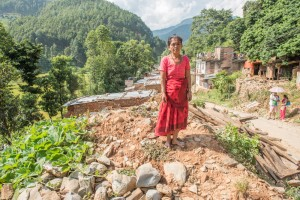 Dipkumari Shrestha standing in the rubble of her former home in Hattigauda